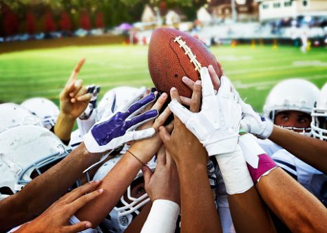 Football players holding up football.